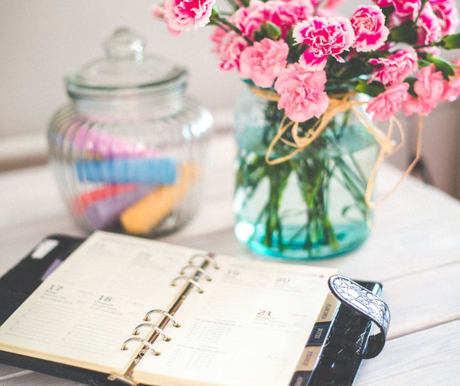 daily planner to be more organized with jar and vase of flowers