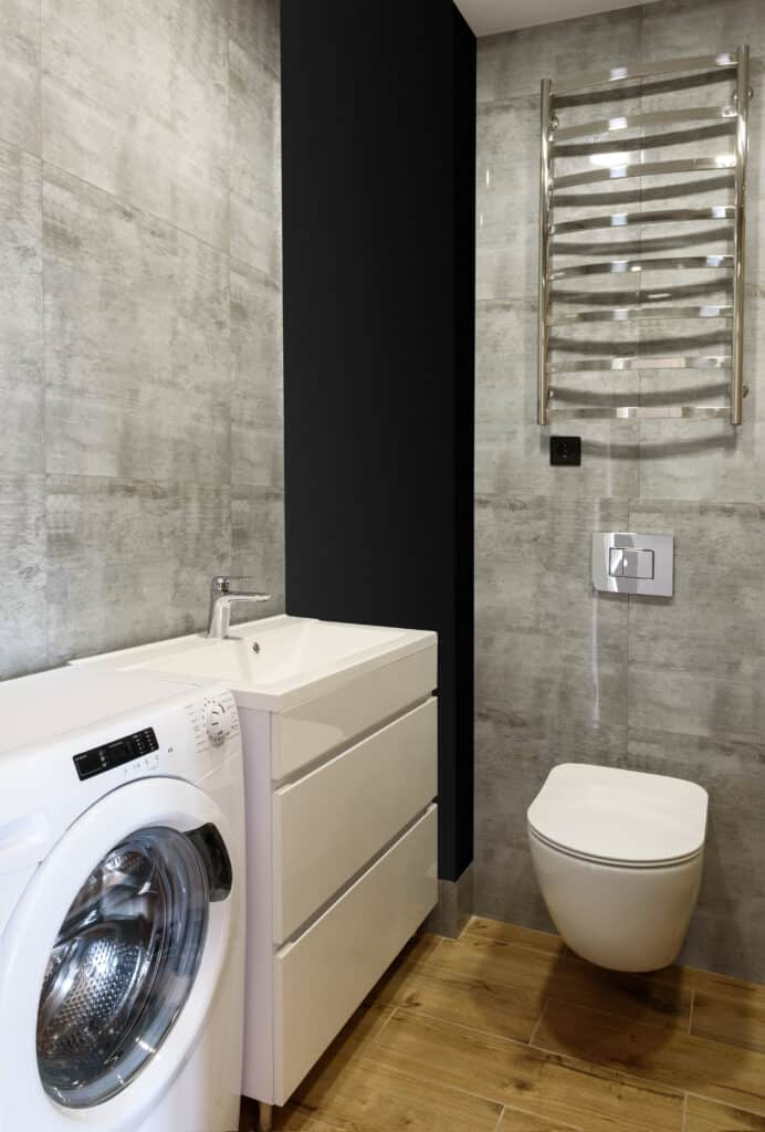 Modern bathroom interior with toilet, white sink, washing machine, gray tile on walls and wood floor space