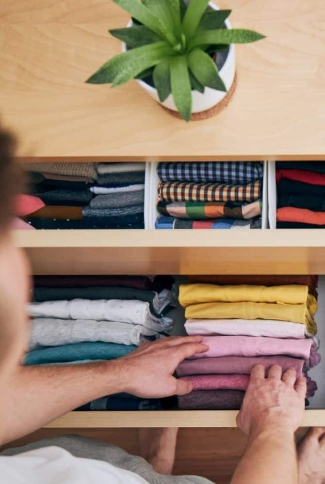 man putting away clothes in a dresser