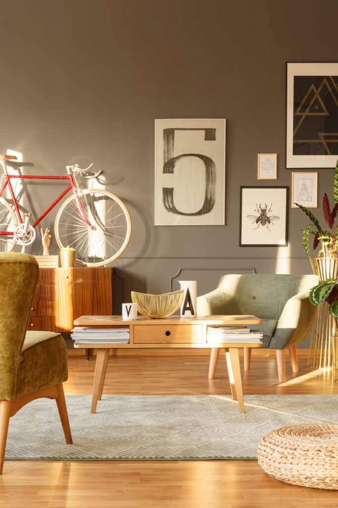 Sun reflections in a hipster living room interior with green armchairs, newspaper table, sideboard, red bicycle and big number five posters on a gray wall.