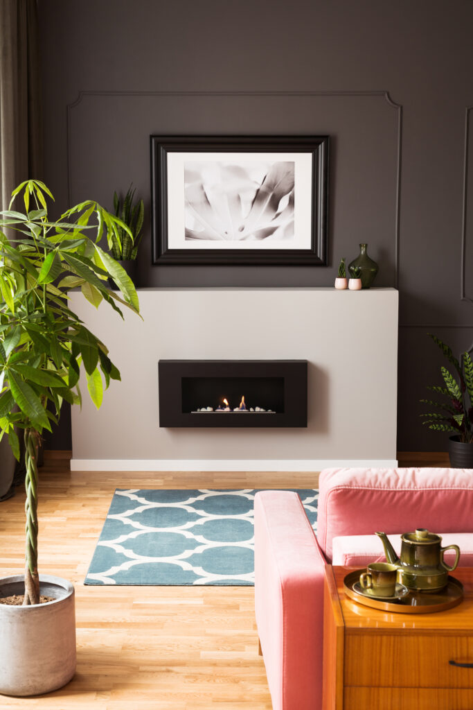 Framed photo above a minimalist, modern fireplace in a stylish living room interior with vibrant and wooden furniture.