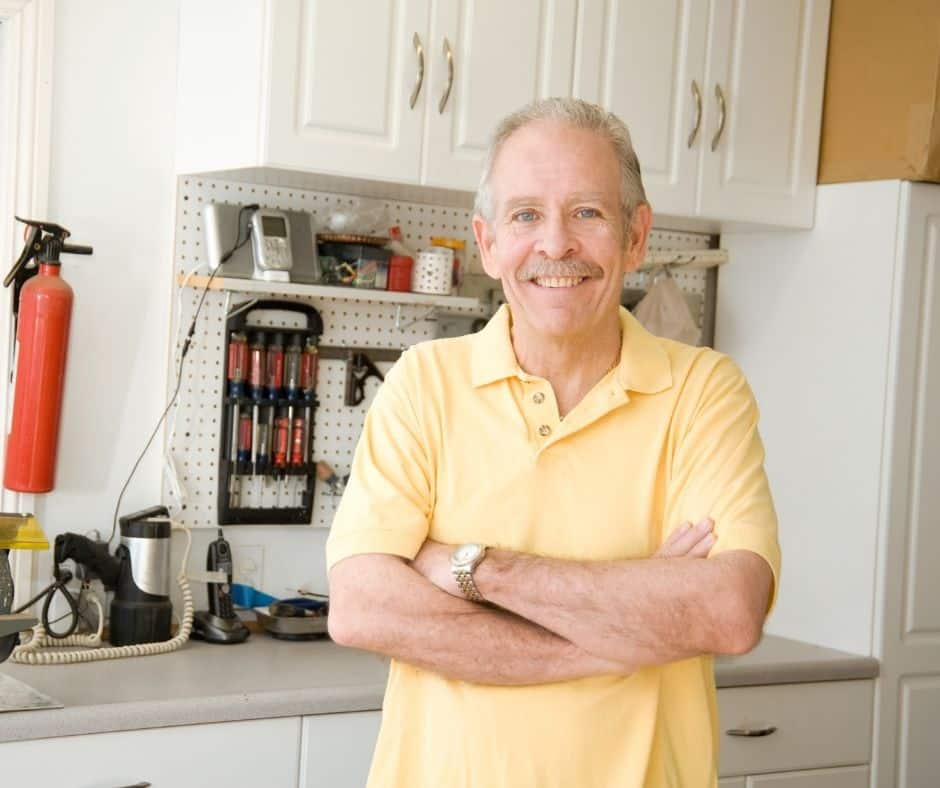 man standing in front of clean garage cabinets and work area