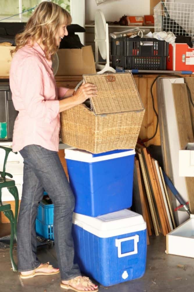 woman standing in messy garage looking in a basket