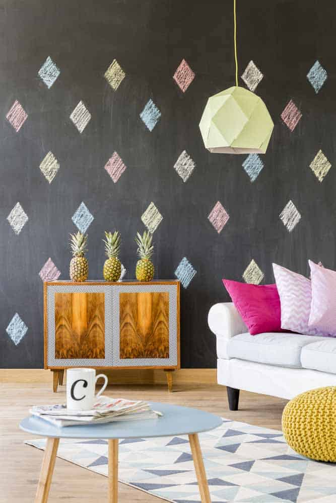 black wall with pink, blue and yellow diamonds stenciled on it, white sofa with pink pillows and cabinet with pineapple on top