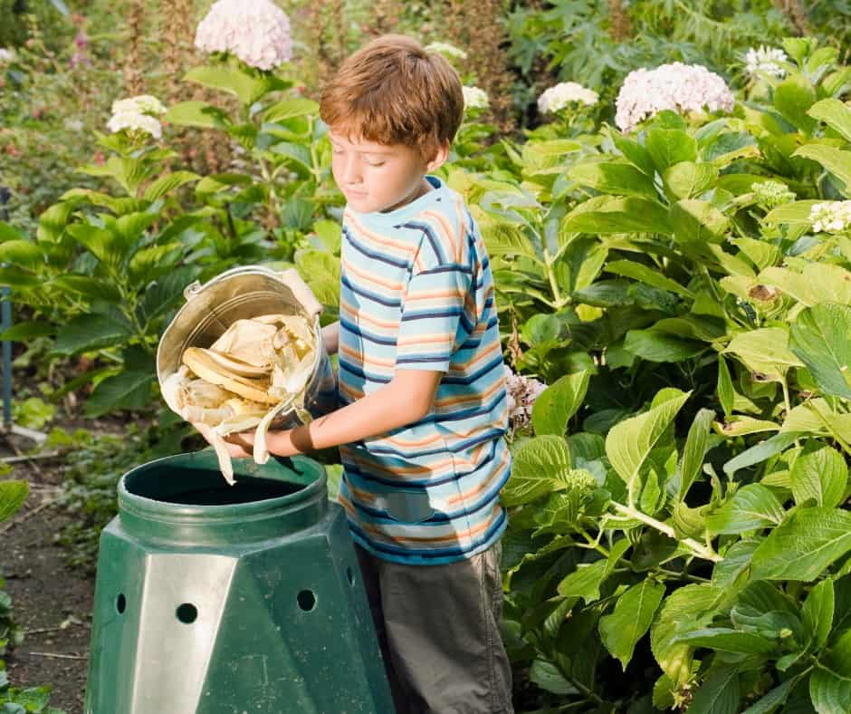boy dumping food into a composter to reduce food waste