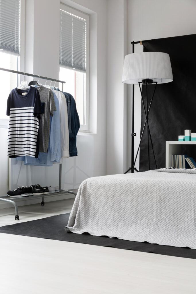 A clothes rack in a studio bedroom