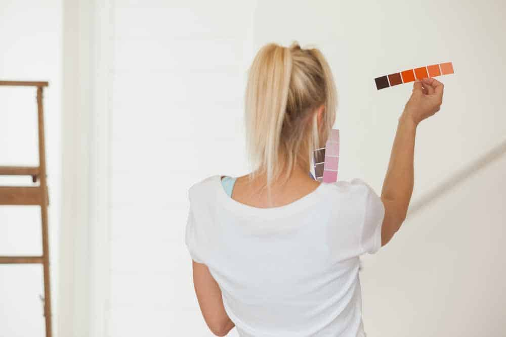 back of woman holding paint swatches up against a wall