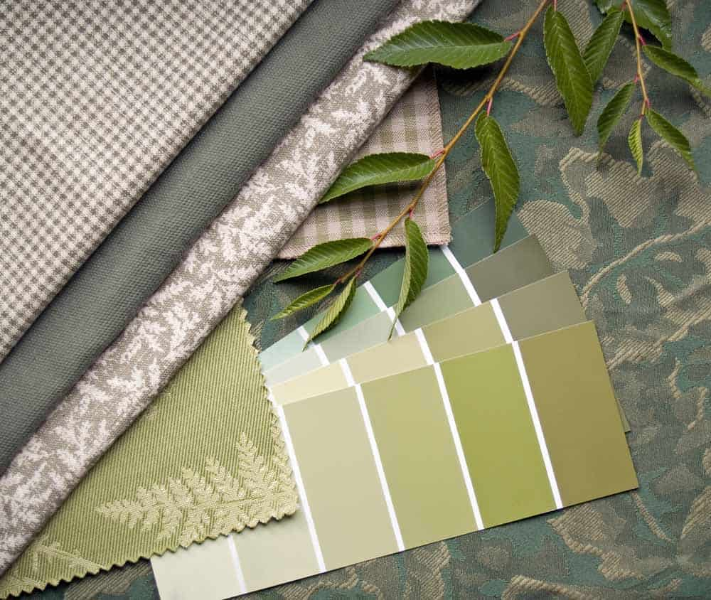 green paint swatches with leaves and printed fabric