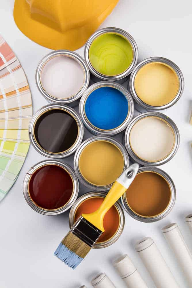 open paint cans with bright colored paint and paint brush