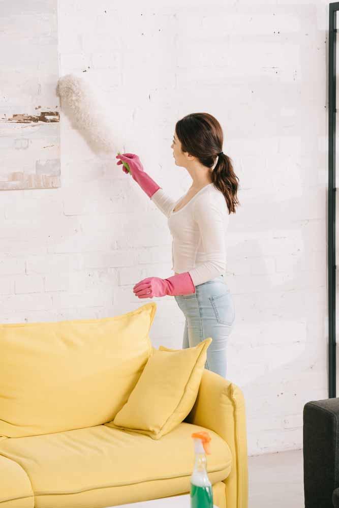 woman dusting behind yellow sofa