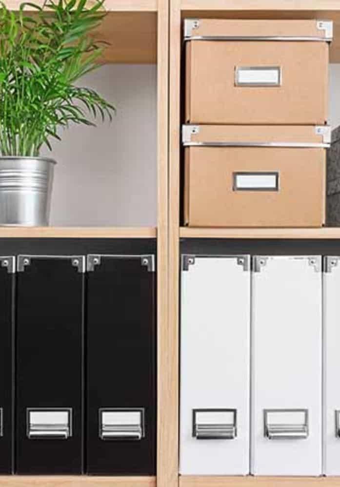 storage boxes and binder on bookshelf