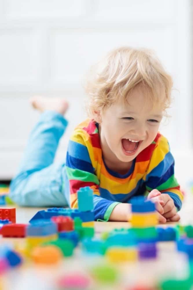little boy playing and laughing on best flooring for families