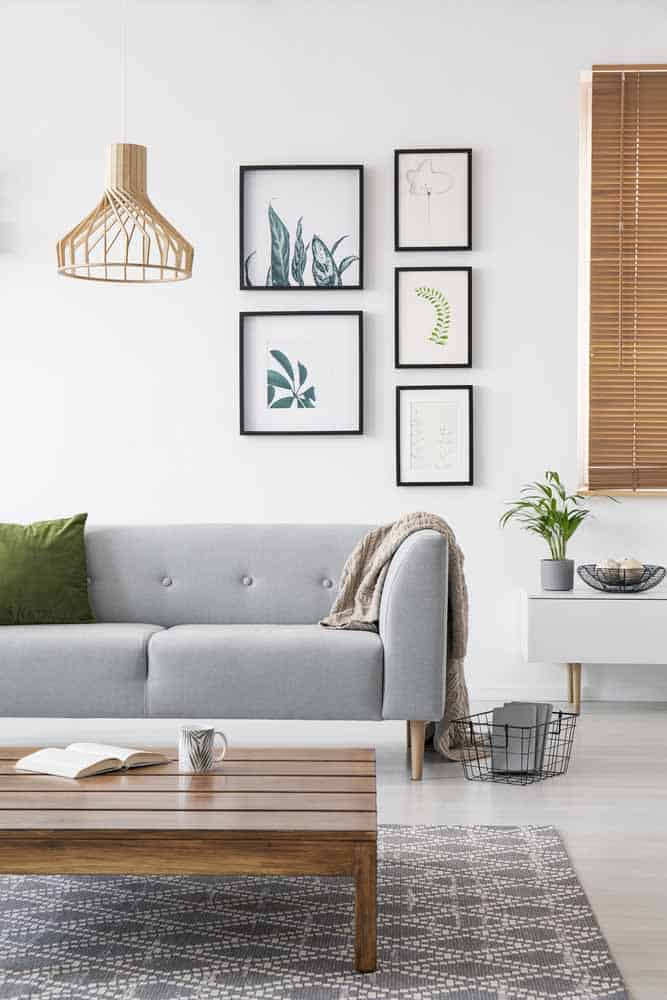 Posters on a wall in a living room interior with a sofa and low coffee table