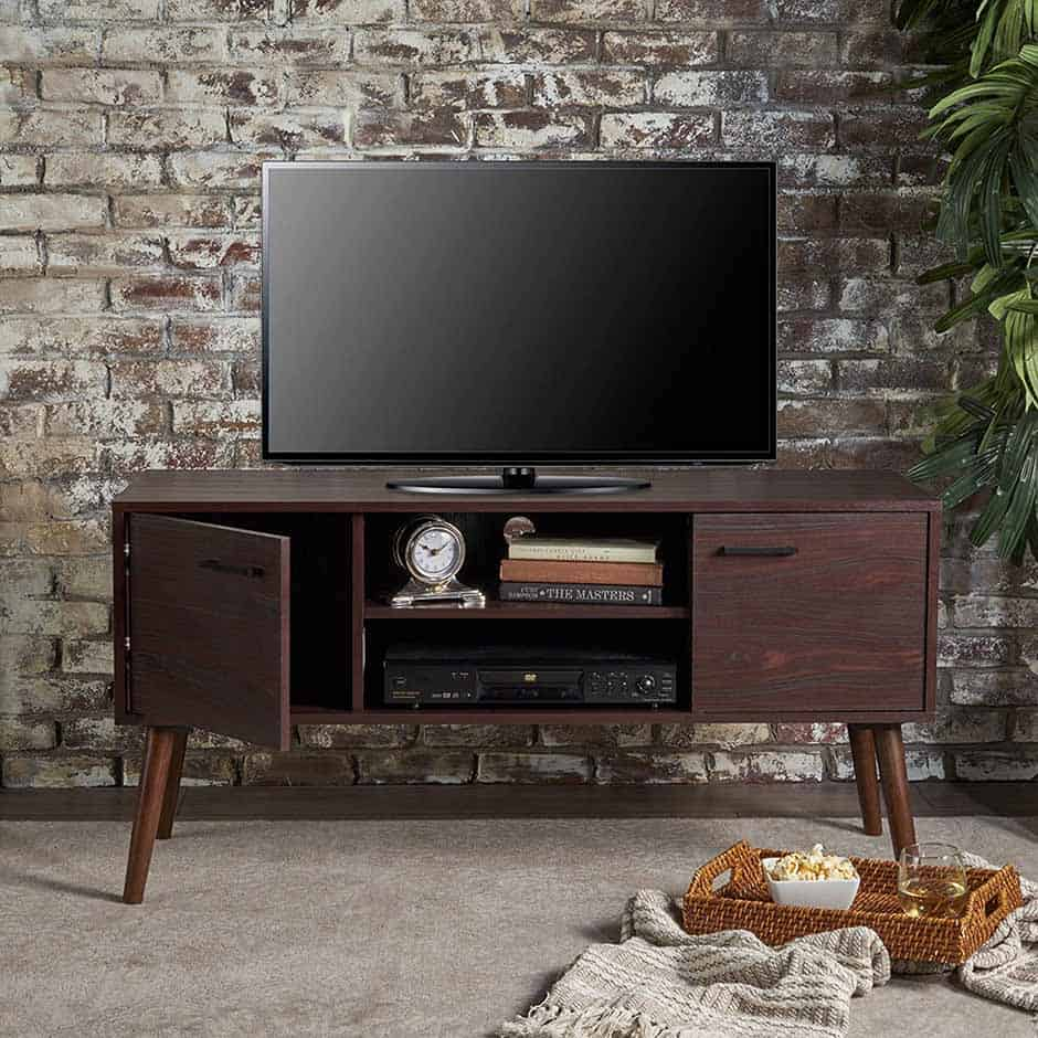 one of the best mid century modern tv stands in front of a faux brick wall