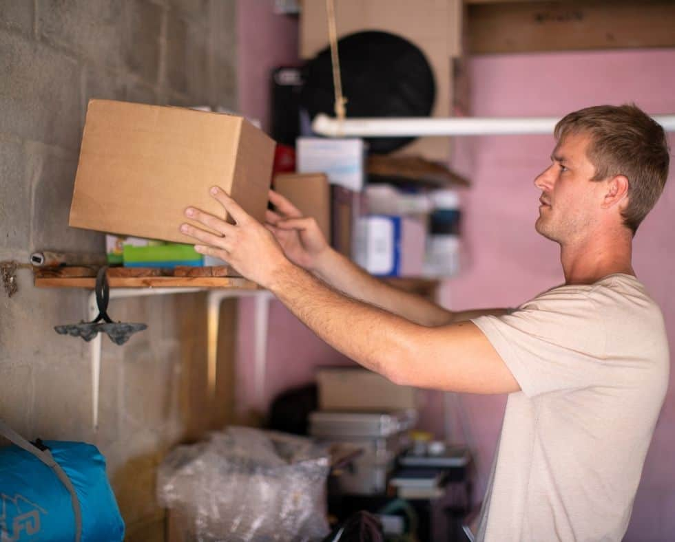 man putting a box on a shelf to declutter your garage