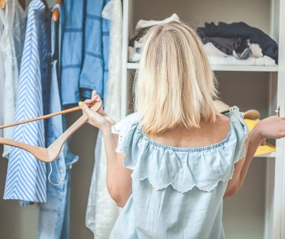 woman standing in front of cluttered closet
