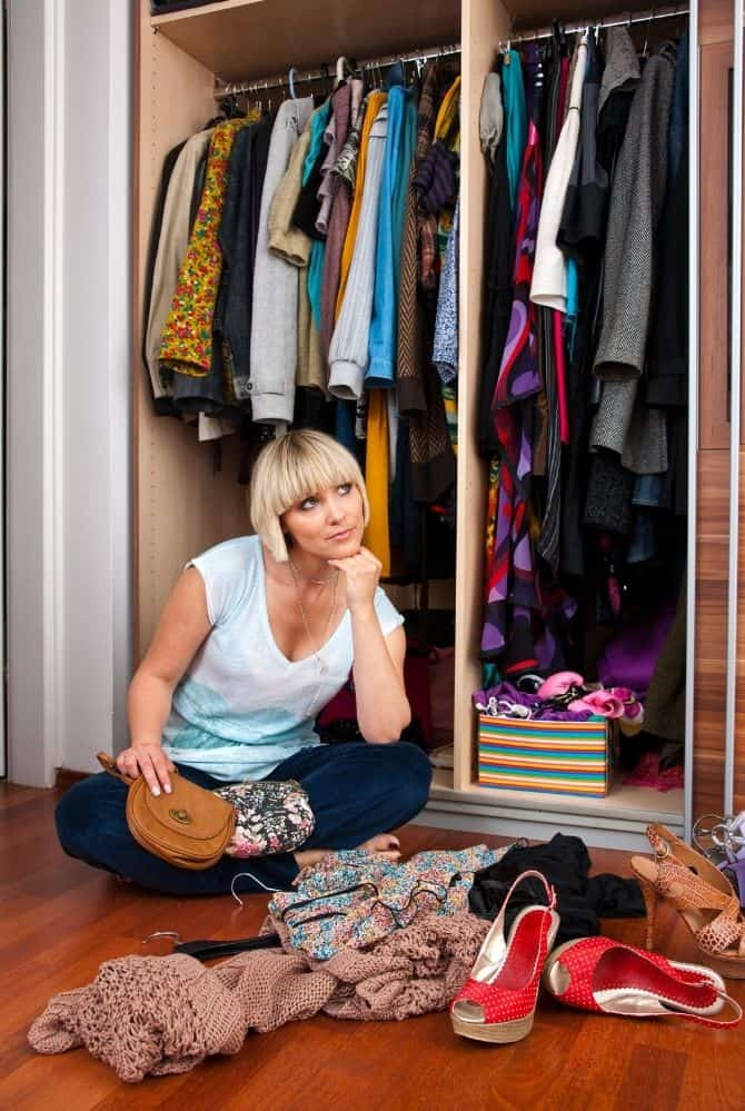 woman sitting on the floor in front of a messy closet
