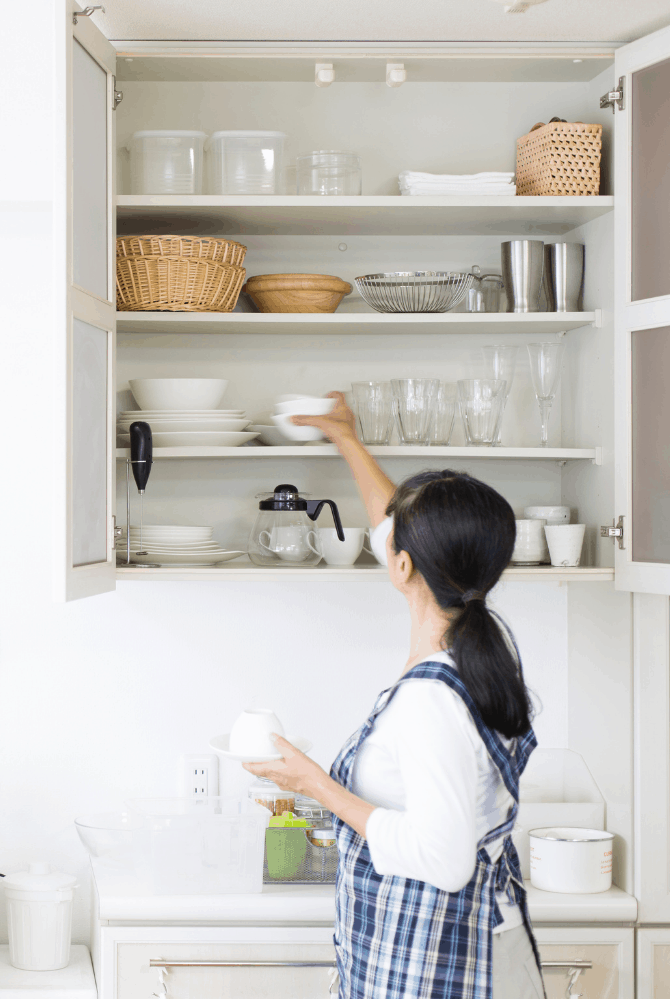 Image of woman decluttering kitchen cabinets